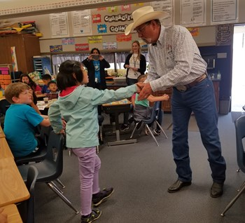 Clovis Rodeo Association President, Ken Elliot congratulating FW student Sunny C. with a handshake on being named a district winner in the 2019 Clovis Rodeo Coloring Contest.