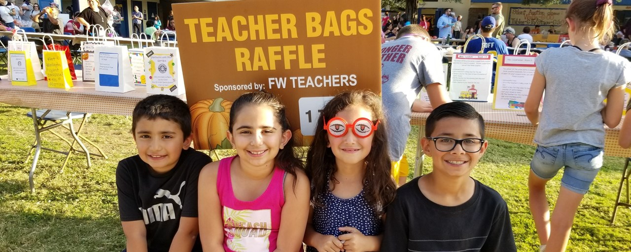 Four students sitting on a bail of hay hanging out by the Teacher Raffle bags at FW School Carnival.