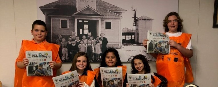 Fort Washington Student Council Members wearing a Kids Day vest and posing for a group photo while holding a Kid's Day newspaper.