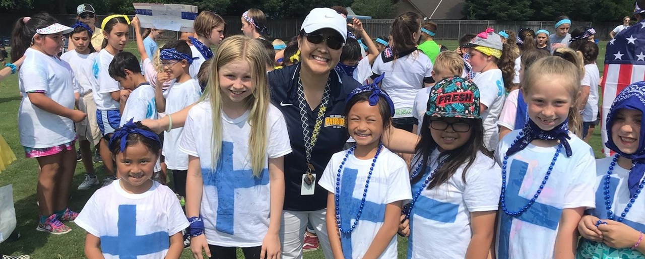 Principal Melanie Hashimoto out at FW Olympic Day posing for a picture with students.