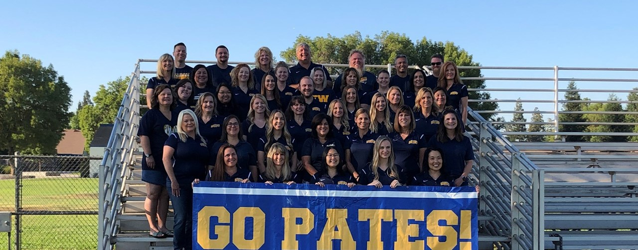 FW staff in a group photo with a Fort Washington sign posing outside on the bleachers for their 2019-2020 staff photo.