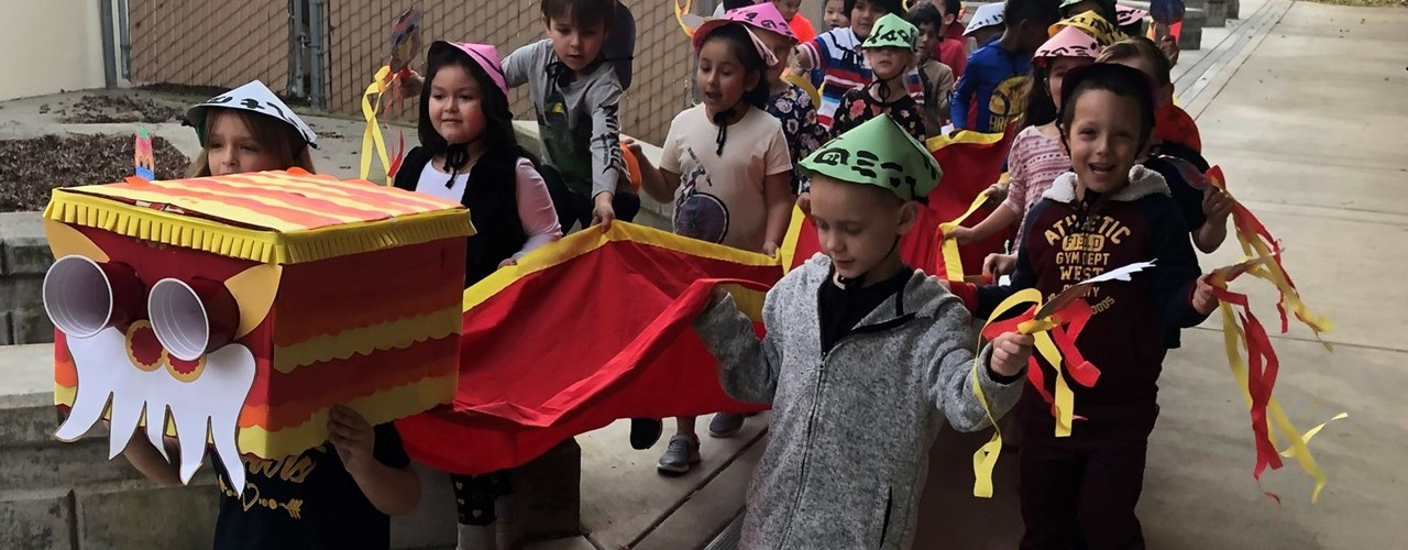 Kindergarten students celebrating the Chinese New Year with a decorative dragon costume