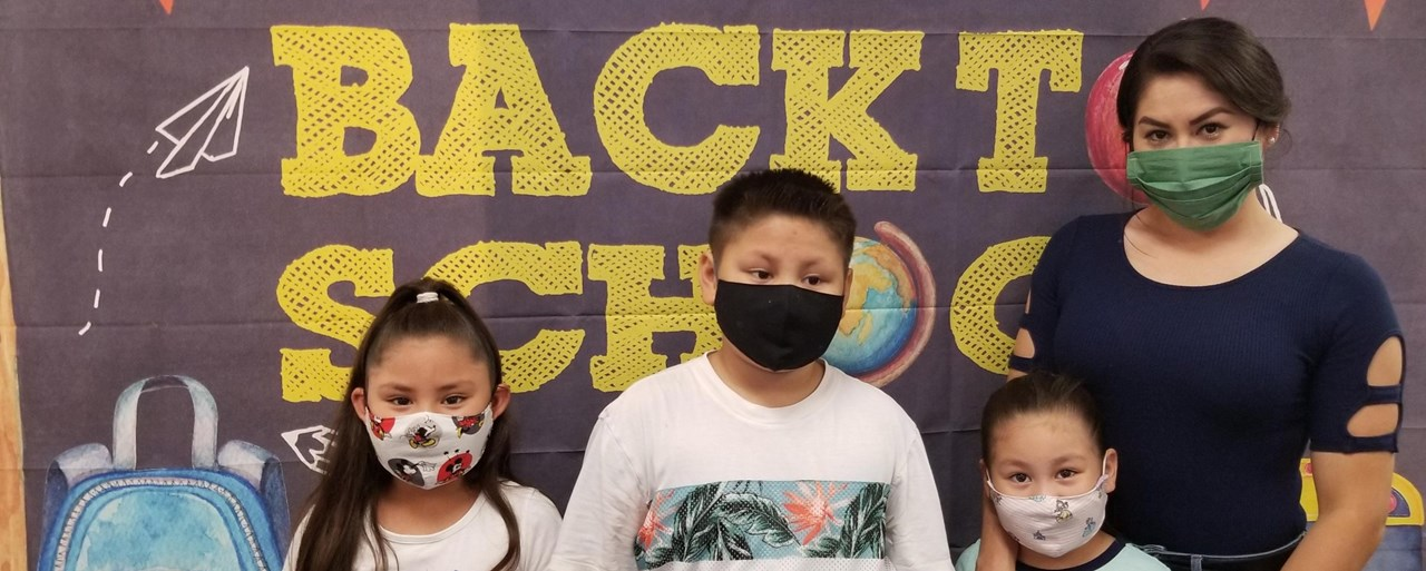 Image of an adult female with 3 scholl age children wearing face masks.