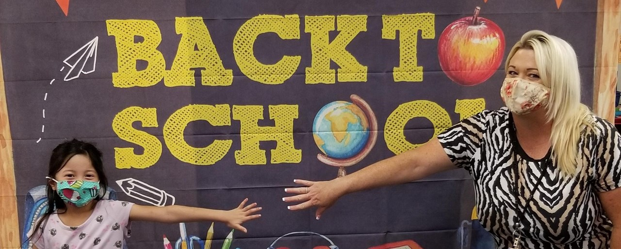 Student and teacher wearing masks standing apart but reaching for each others hands in front of a Back to School sign.