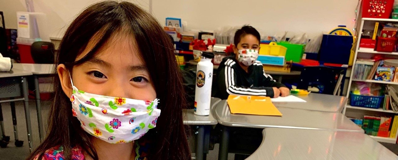 Image of students wearing masks while doing school work at a their desks distanced away from each other.