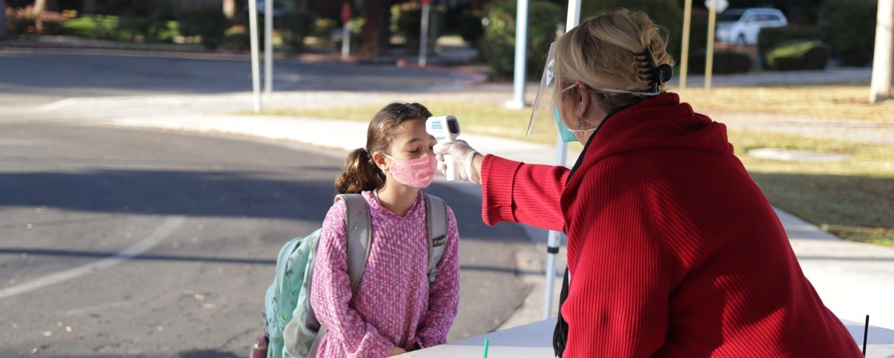 Image of a student getting screened with a temperature check before going to class.