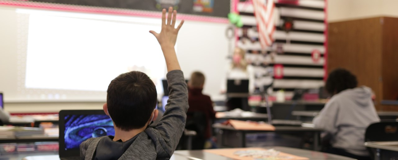Image of a student raising his hand in class while being socially distant from other students.