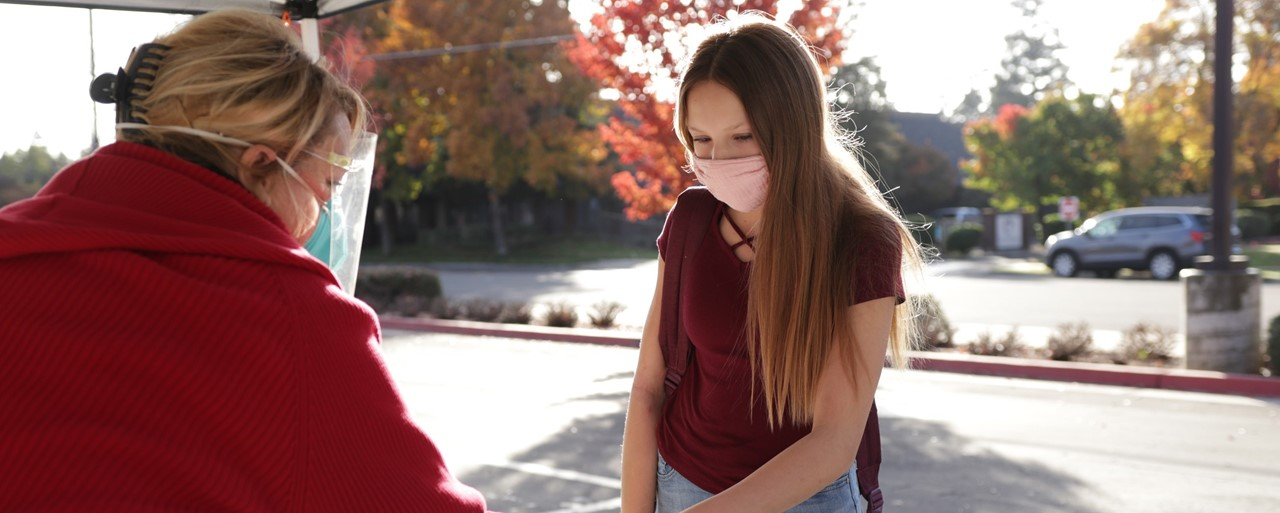 Image of a student getting screened for wellness before going to class.