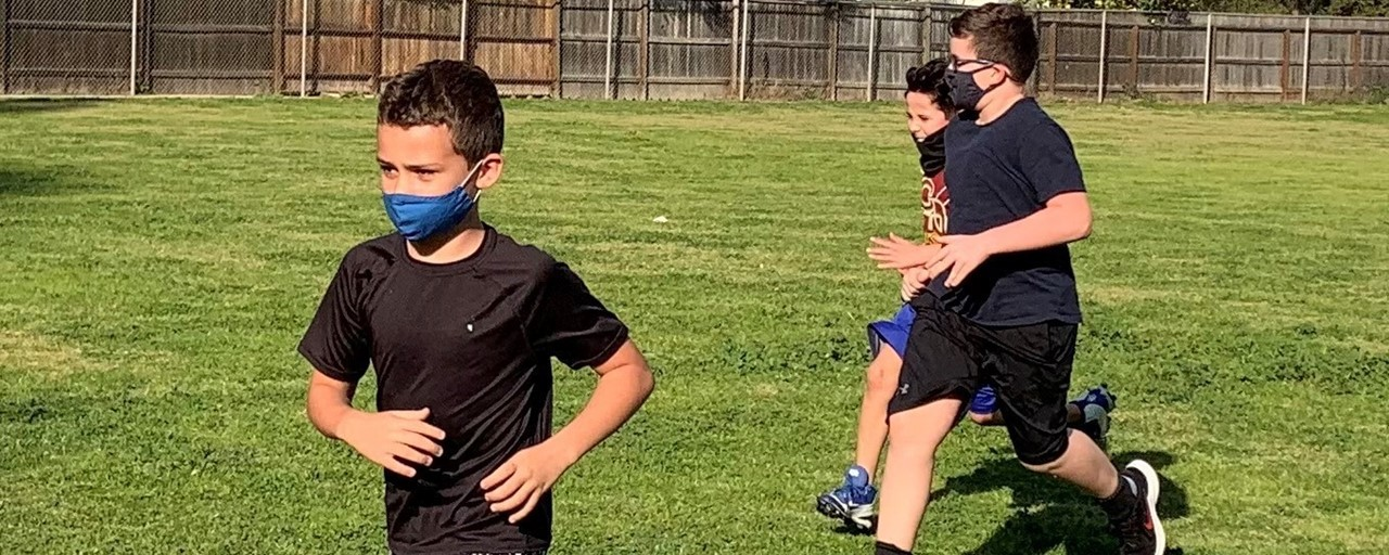 FW students wearing mask while running on the football field during sports training practice.