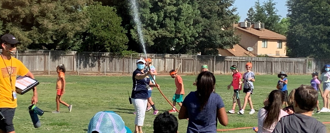 Image of FW Olympic Day events with Mrs. Hashimoto spraying water to keep things cool.