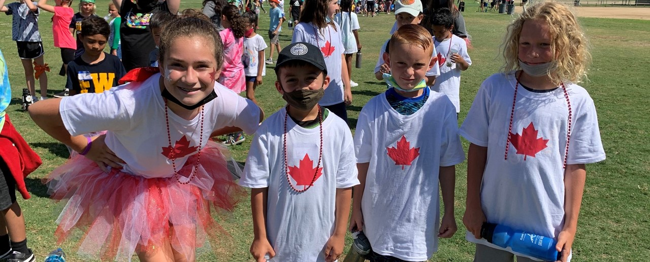 Image of FW Olympic Day events with four students standing together with a maple leaf painted on their shirts.