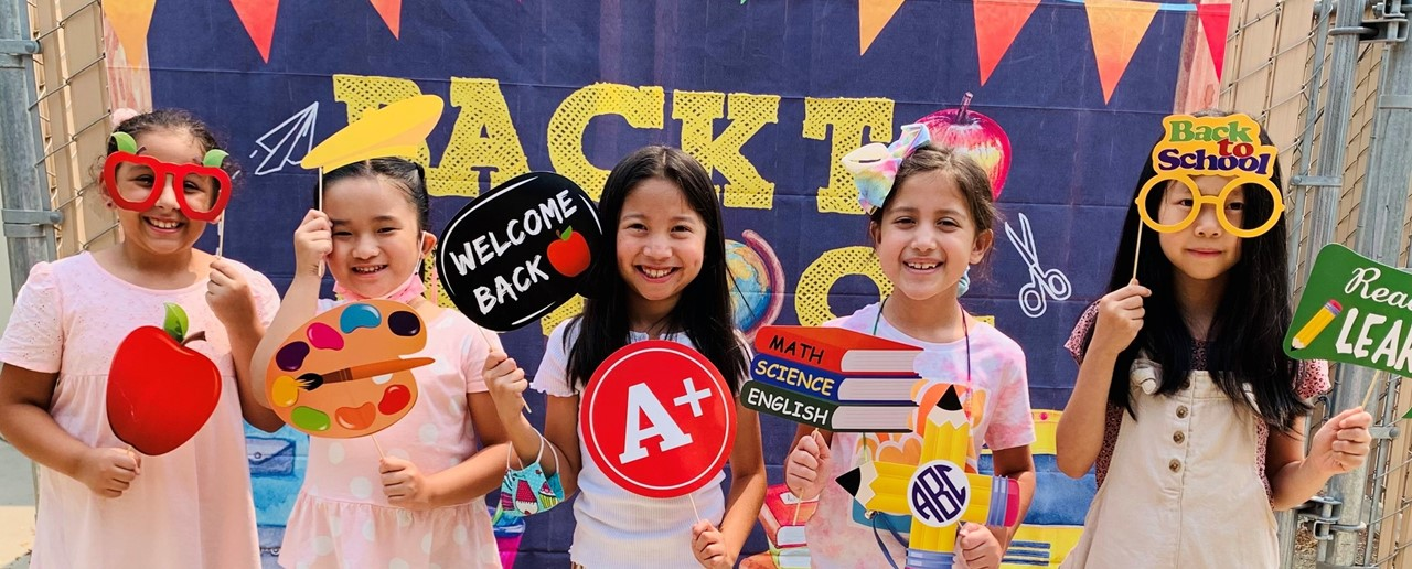 Image of five second grade girls outside, holding up back to school photo props.