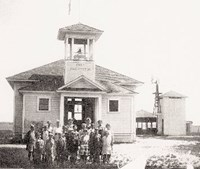 photo of original Fort Washington school house with its first students standing in front of it.