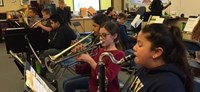 Photo of students playing instruments during a practice session.