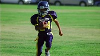 Image of a FW football player running on the field.